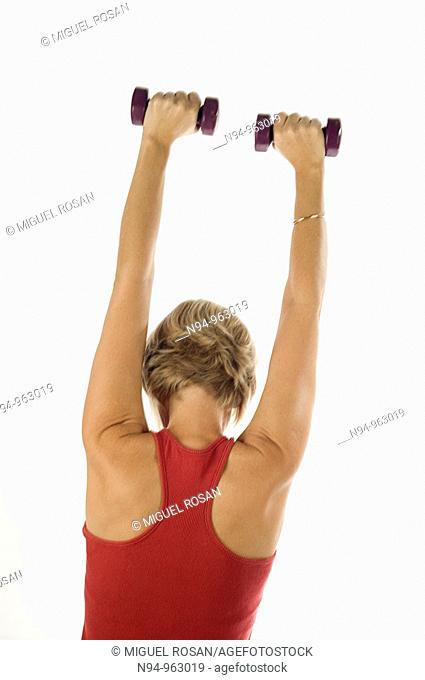 Young woman, blonde, exercising with weights in the gym to get fit