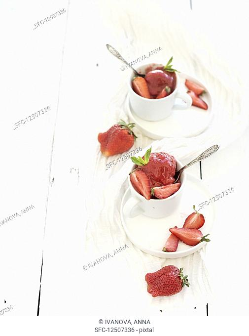 Strawberry sorbet ice-cream with mint leaves in cups over rustic white wooden background