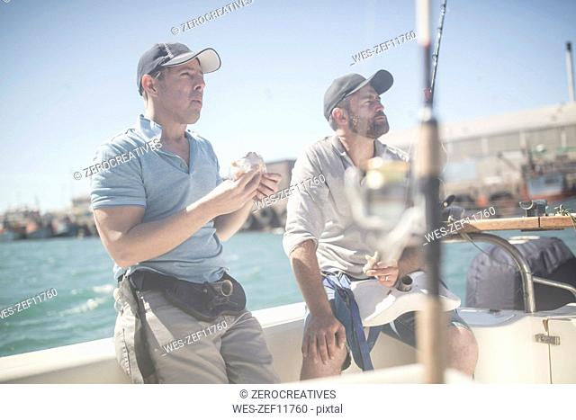 Two men having lunch break on boat with fishing rods