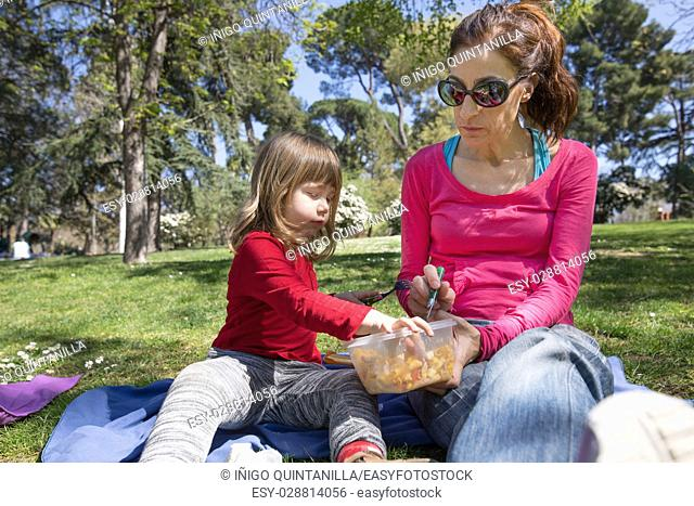 woman mother and three years old blonde child, sharing and eating pasta salad with fork from plastic container, as picnic