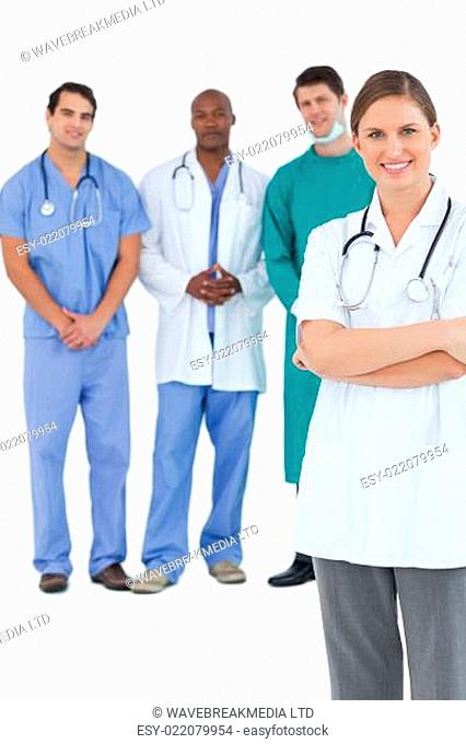 Smiling doctor with folded arms and colleagues behind her