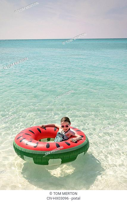 Portrait girl floating in watermelon inflatable ring in sunny tropical blue ocean