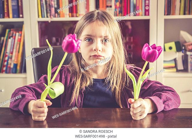 Portrait of pouting little girl with two tulips in her hands