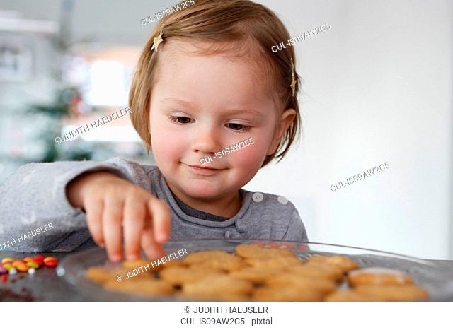 Girls looking down selecting fresh baked cookie smiling