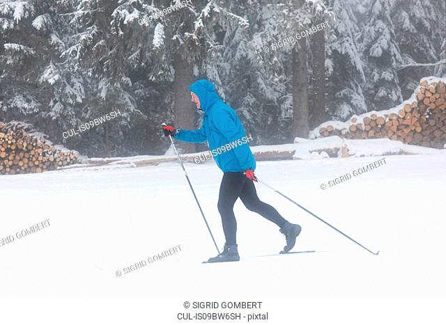 Mature man cross country skiing in forest, full length