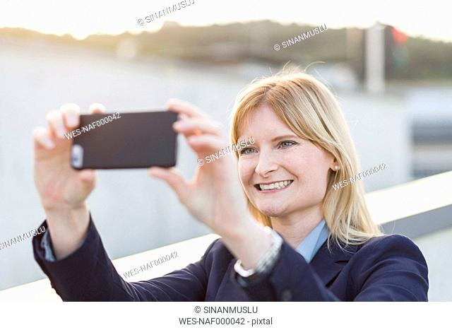 Portrait of smiling blond businesswoman taking selfie with smartphone