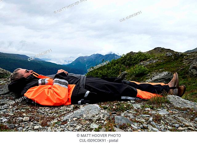 Senior male hiker taking a break lying on top of mountain, side view, Valdez, Alaska, USA