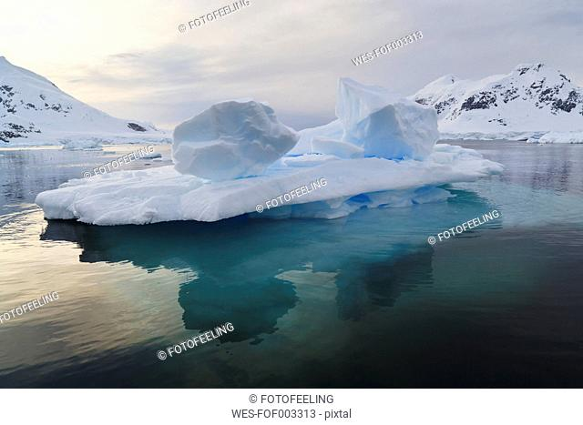 South Atlantic Ocean, Antarctica, Antarctic Peninsula, Gerlache Strait, Blue iceberg and Snow coverd mountain range at paradise bay