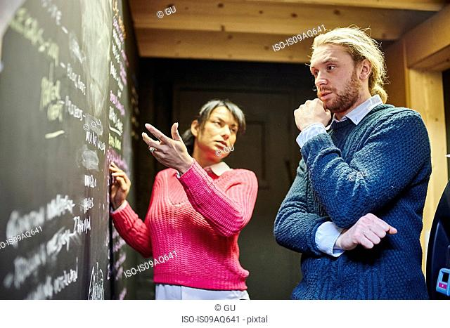 Man and woman discussing ideas in front of blackboard in traditional workshop