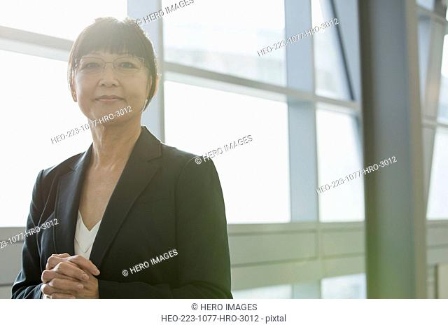 Portrait of confident businesswoman with hands clasped