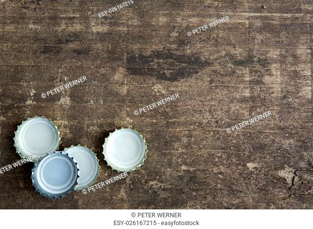 four bottle caps on a rustic wooden board