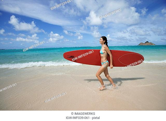 A young woman walking on beach with surfboard