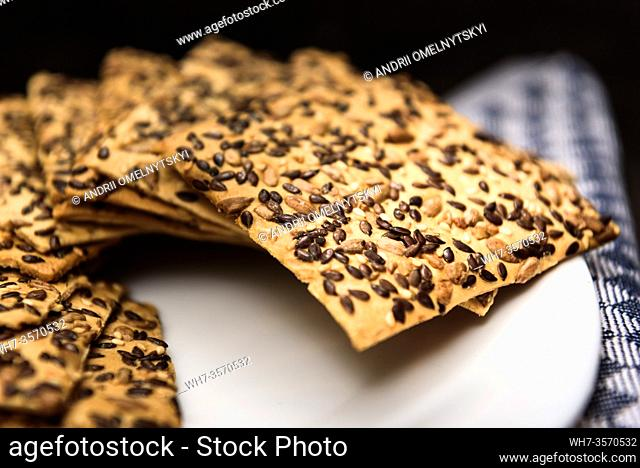 cookies with sunflower seeds and sesame seeds on a white plate with checkered napkin