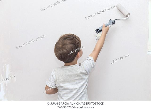 3 years cute little boy with paint roller in hand. Kids Helping House Chores concept