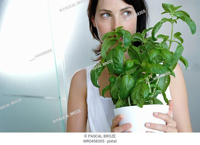 Close-up of a mid adult woman holding a flower pot and looking sideways