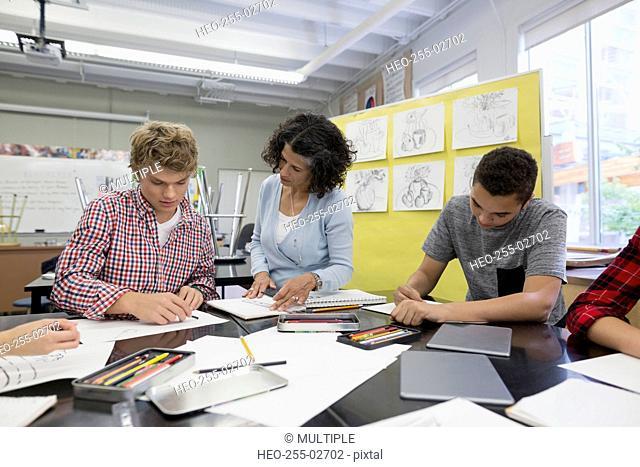 Teacher helping high school student in art class