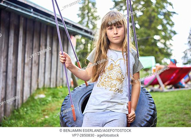 young girl leaning against tire swing at playground
