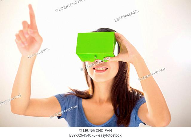 Asian Woman wearing virtual reality device and finger want to touch something