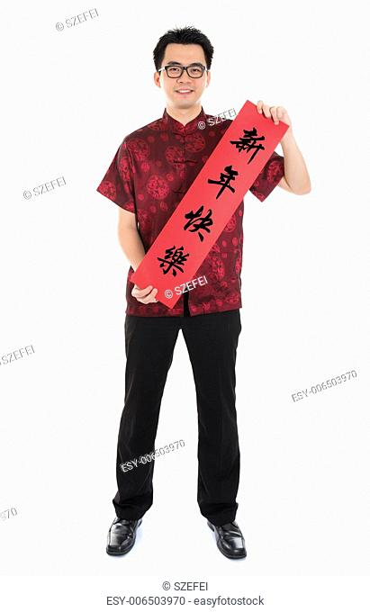 Full length Asian man with Chinese traditional cheongsam or tang suit holding couplet, the Chinese word means Happy New Year