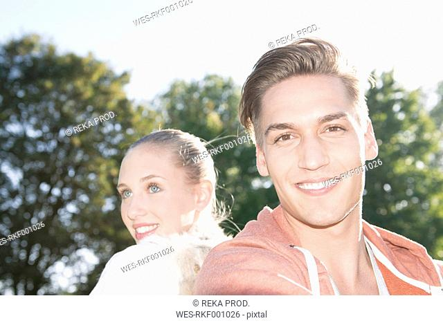 Portrait of young couple sitting back to back on a meadow