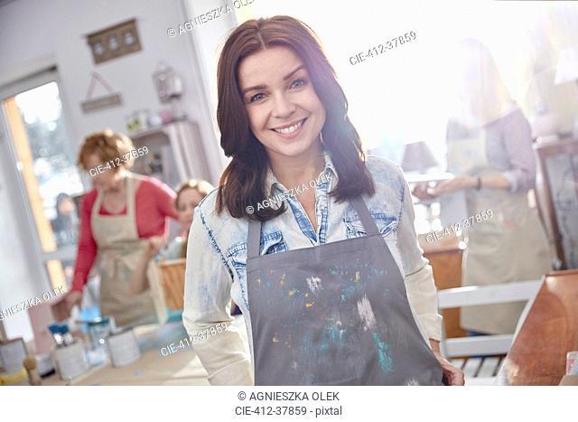 Portrait smiling, confident female artist painting in art class workshop