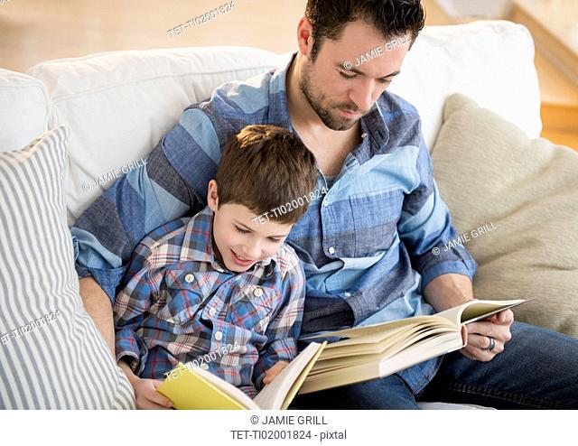 Father reading books with his son (8-9)