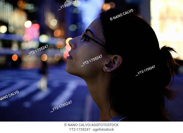 Young cute woman in Fifth Avenue at night