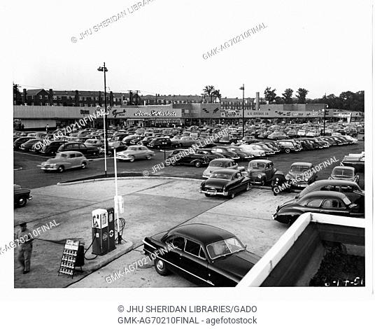 Photograph of the parking lot for the Northwood Shopping Center in Baltimore, Maryland, showing many cars and commercial buildings such as Acme Markets