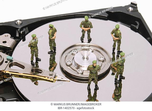 Hard drive with miniature police figures, symbolic image for data protection