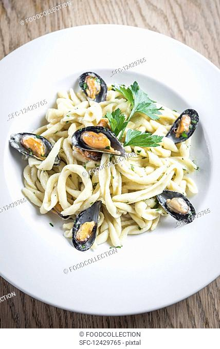 Traditional artisanal homemade fresh pasta with mussels and a creamy pecorino cheese sauce garnished with parsley in a white plate