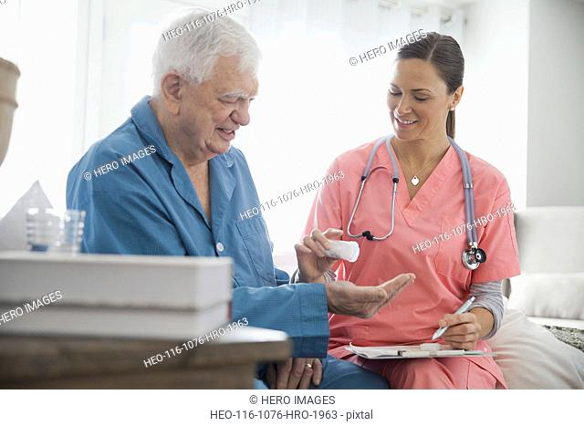 Home nurse giving pills to senior patient