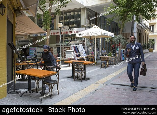 25 May 2020, Greece, Athen: A waitress arranges the tables in a restaurant in the centre, as the cafés and restaurants are opening again today
