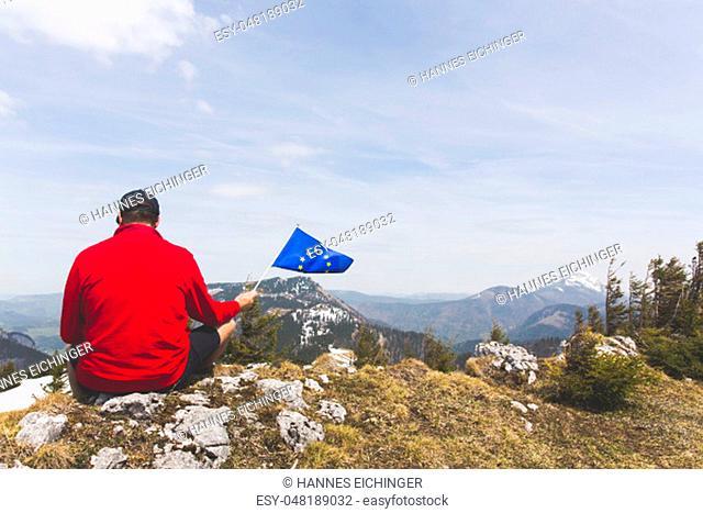 male hiker with red sweater and flag from the european union outdoor somewhere in the austrian alps