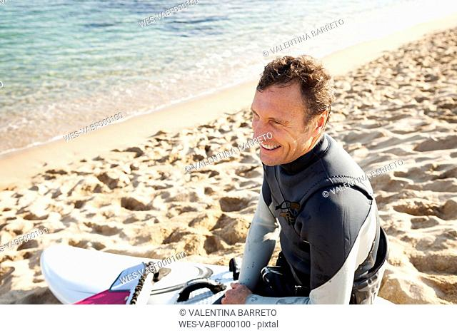 Smiling man on the beach with surfboard
