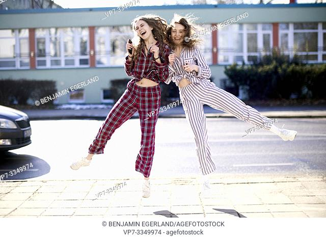 two exuberant women jumping against each other, wearing pyjamas at street