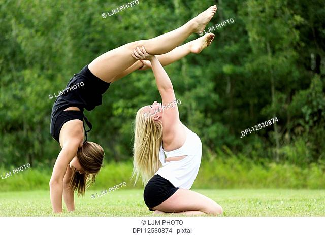Two Teenage Gymnists Practicing Their Routines Outdoors In A Park And Doing Handstand Partner Balances; Edmonton, Alberta, Canada