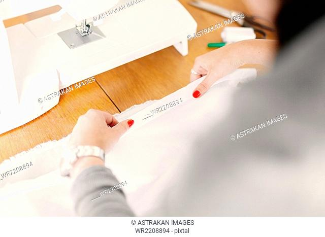Cropped image of designer holding pinned up white fabric at table