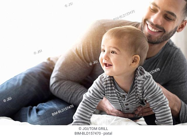 Smiling father playing with baby son on bed