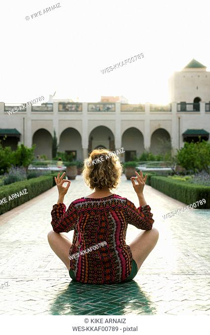 Morocco, Marrakesh, tourist sitting on the floor in a courtyard doing yoga