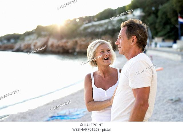 Senior couple relaxing on the beach at evening twilight