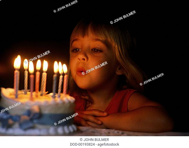 Young girl bowing out candles on birthday cake in dark light