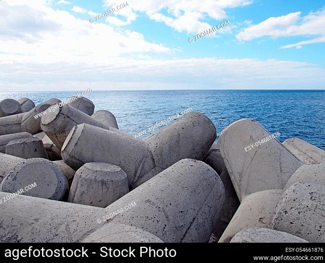 concrete interlocking tetrapods used to prevent coastal erosion placed on a shoreline with a blue sea and sunny sky