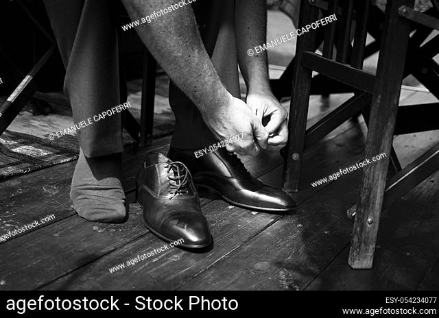 Hands of groom and shoes