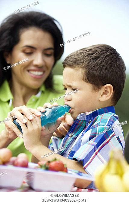 Close-up of a woman helping her son drink water from a bottle