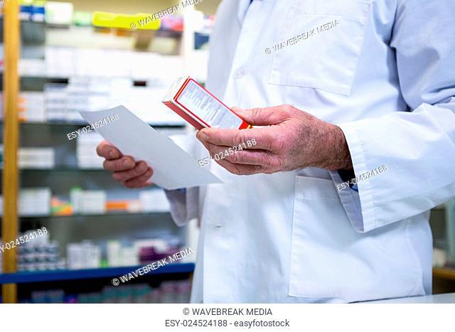 Pharmacist holding a prescription and medicine