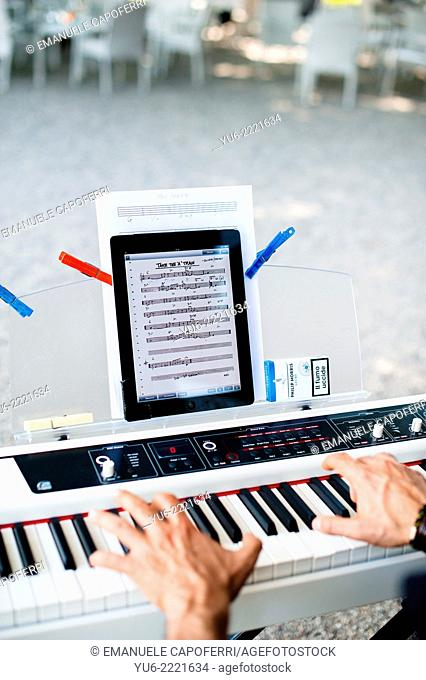 Pianist plays electronic keyboard, ipad as sheet music
