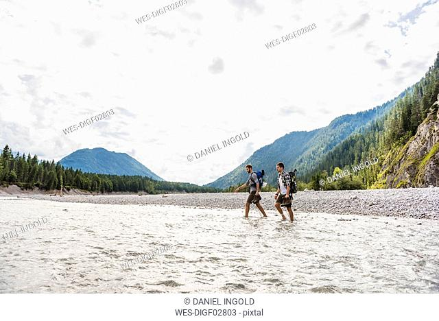 Germany, Bavaria, two hikers with backpacks crossing Isar River