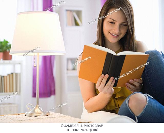 Young woman reading book in living room