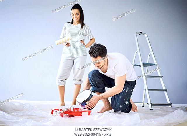 Happy couple painting in apartment together