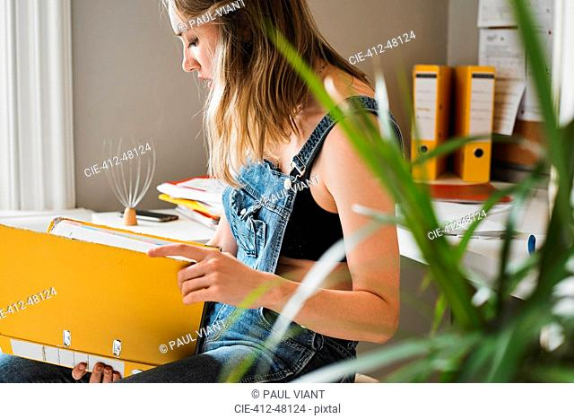 Young female college student with binder studying